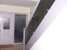 Grey tinted toughened glass panels used in a domestic staircase application.
