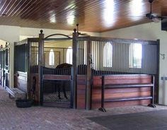 Great idea for corner stalls. Opens up the aisle and is safer for the horses. I would have an open top door for the horse to hang his out though. Gorgeous stalls!