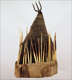 Shaman hat, Nepal.  Rare example of Nepali Shaman hat. Nepali shamans - Jankhri & Dhami who are spirit mediums and shamanic healers often have headgear with bird feathers or porcupine quills, kauries and coins attached. The trisule, an iconic symbol for Shiva, at the crest is also frequently incorporated into their costume. Often those shamans are from the Tamang (and perhaps also Magar) ethnographic groups in NW Nepal.  Materials: cloth, porcupine quills, kauries, iron and coins.