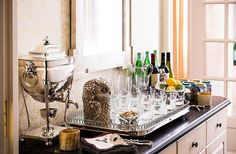 This Top Designer's Holiday Hosting Tips Are the BEST --  Get the ultimate Christmas decorating tips from Italian decorator Alessandra Branca, who goes all out with her red, white and green Christmas decor, like this festive and traditional bar sideboard with antique sterling silver and glassware shown here. Read more and see the full dinner party decorations on our Style Guide!
