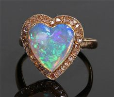 18 carat gold opal and diamond ring, the heart shaped opal with a diamond surround, ring size O - Stock Ref:932-19
