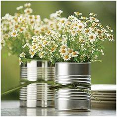 Latas de leite em pó ou achocolatados podem se tornar um lindo vaso de flores. Aproveite para enfeitá-lo usando fitas.
