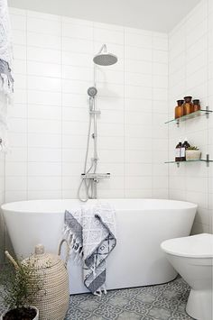 a very small bathroom with a patterned grey tile floor and a freestanding tub for a chic look
