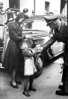 Germany, Himmler shaking hands with a German child.    I wonder if they saw this photo later in life and realized that they had looked evil straight in the eye as a child.