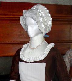 "Brown silk round gown with accessories. A frilled 'tucker' edges the low neckline, and a strand of plain ""gold"" beads are worn, tied in back with a ribbon. A fine linen apron ties about the waist, and has a ""pinner"" top and pointed center waist front .Either a plainly-dressed mistress or an upper-class  housemaid, the lady wears a very full, round-eared white linen cap with ruffles and frills over her bouffant hairdo."