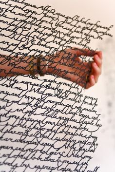 Annie Vought cuts away the white paper between the ink of handwritten texts