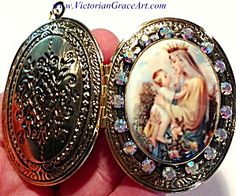 $89 Vintage large size gold tone locket with porcelain center cameo featuring the Blessed Mother Virgin Mary wearing a crown in a garden of pink roses and holding the Child Jesus. The cameo is surrounded by Aurora Boraelis rhinestones  The locket can be used as prayer petition request jewelry or on an altar / shrine.
