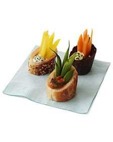 Individual Crudites: A hollowed-out slice of baguette houses crunchy crudites that are served with a trio of dips.