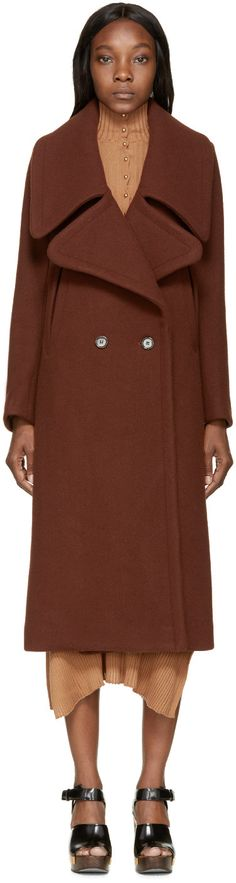 Long sleeve double-breasted wool coat in maroon. Wide peaked lapel collar. Button closure at front. Diagonal welt pockets at front. Partially lined. Tonal stitching.