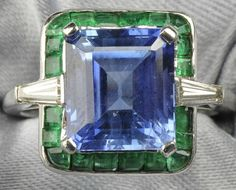 Ring is set with an emerald-cut sapphire measuring approx. 10.40 x 9.20 x 6.10 mm, flanked by tapered baguette-cut diamonds and framed by fancy-cut emeralds. Unique shape, stunning color combination.
