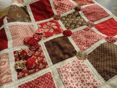 Simple patch quilt with yo-yo's at intersections of strips - from: Rozen en Ruiten. Sweet!