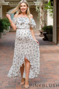 A floral print chiffon maternity dress featuring a slit front hi-low hemline with a ruffle trim, a cinched elastic off shoulder neckline and waistline, short sleeves, and double lining to prevent sheerness. This style was created to be worn before, during, and after pregnancy.