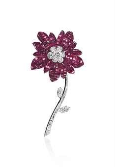 A RUBY AND DIAMOND 'MAGNOLIA' BROOCH, BY VAN CLEEF & ARPELS  The flowerhead with mystery-set ruby petals and brilliant-cut diamond pistil, to the detachable baguette-cut and marquise-shaped diamond stem and leaves, 1968, 10.0 cm