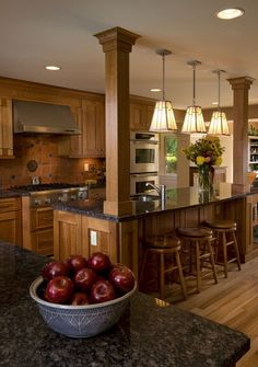 Traditional White Creative Kitchen Design Inspirations with Large Wood Kitchen Cabinet that have Useful Storage Space and Great Wood Kitchen Island that have Elegant Black Granite Countertop complete with the Stools also Three Classic Pendant Lamps Decorating Lighting