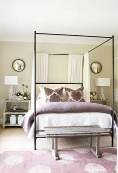 Atlanta Homes Mag    Beautiful purple bedroom design with soft tan walls paint color, iron canopy Oly Studio Marco Bed, purple blanket, purple pillows, Madeline Weinrib Atelier Lilac Song Rug, white washed step tables and white branch lamps.