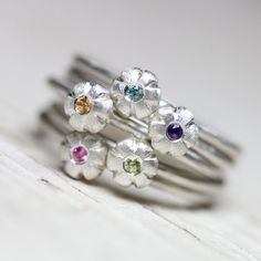 A gorgeous stack of floral gemstone rings! Sunset Bouquet is so much fun and could be the start of a long lasting relationship. Get one cute little flower ring with the gemstone of your choice or get the whole stack, why not?!  Your gemstone choices are: Pink Sapphire Yellow Sapphire Purple Amethyst Green Peridot Blue Zircon (all 1.5mm)  Shown in size 7 or 55 or 17.5 *Made to order in your size (please allow 3-5 business days) nangijalajewelry.etsy.com  **Listing is for one (1) ring