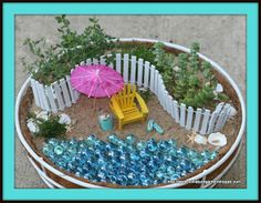 Miniature beach garden.  This would make a great gift for someone who loves the beach.  You could even scoop up some real sand at your favorite beach to make it all the more special.  The use of blue marbles makes it more realistic.  I would even mix in sea green marbles with the blue for a more tropical water scene.  You could paint popsicle sticks white and create the fence.  I would choose a different substrate type behind the fence area and plant more exotic miniature plants.