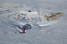 An aerial view of Amundsen-Scott South Pole Station.  The silver geodesic dome was dedicated in 1975 as the second station to be built at the South Pole.  It provided wind shelter for smaller buildings under it.  Decades of accumulating snow drift, and growing scientific population, resulted in the decision to build a new station, seen at right, still under construction when this photo was taken.