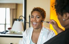 This bride is all smiles getting her makeup done on wedding morning. | essence.com
