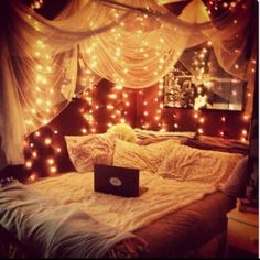 fairy lights and white tulle canopy against red walls & bedding, B&W image