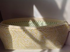 This cute zippered case has beautiful yellow/cream swirly designs, lined with a green polka dotted interior. The shape of the case is sleek with curved corners at the top towards the zipper for a secure side-to-side closing. The bottom edges are straight with gentle, rounded corners to the bottom. This case is flat overall.  It measures approximately 9.25 inches wide and 4.25 inches tall (23.5 cm x 10.8 cm).