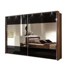 Prunk trifft moderne Formen: Dieser ausladende Schwebetürenschrank mit schwarzen Hochglanzfronten und einem imposanten Spiegel bietet massig Platz für all Deine Klamotten und besticht zudem durch die eingebaute Beleuchtung.