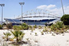 Abandoned;  Palms and other wild vegetation now inhabit the beach volleyball Olympic stadium in Athens.    Super Creepy Pictures Of Forgotten Olympic Villages