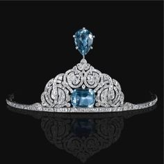 Aquamarine and diamond aigrette tiara, Cartier, 1912.  Centering on a cushion-shaped aquamarine within an arched surround of interlaced open work scrolls millegrain set with circular- and rose-cut diamonds, surmounted by a pear-shaped aquamarine, signed Cartier Paris, Londres, New York.. Est. 120,000—170,000 CHF. Provenance: From a European collection - formerly in the collection of Olga, princess Paley, countess Hohenfelsen.