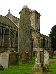 Rudston Church in East Yorkshire, England. With the late Neolithic or early Bronze Age, Prehistoric Standing Stone, which is the oldest in Britain and almost 8 metres high. All Saints Church was built in 1100