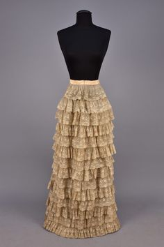 WORTH BUSTLE DRESS with TWO BODICES and CAPE, 1880. Ivory silk damask,  sleeveless back-lacing evening bodice with ecru lace, having deep point and decorated with white beads, trained bustle skirt with fringed center panel, trimmed with self pleats, train edged in satin, underskirt of muslin with fourteen lace ruffles, satin cape with tulle overlay beaded and sequined in an allover floral, satin trim and plush lining. Gold printed petersham label. Under skirt