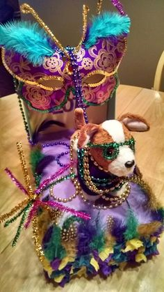 Mardi gras kids float! Shoe box, construction paper, beads, piping, and your imagination!!!  The siding is made with small squares of tissue paper- glued at the center and crinkled around it!   The fireworks are twisted piping in different colors. The kids really wanted their doggie to be on the float, so we added it, put glasses on it for flare, and strung beads throughout! Easy!