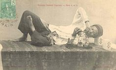A postcard from French Indochina showing a Vietnamese opium smoker with a modest layout.