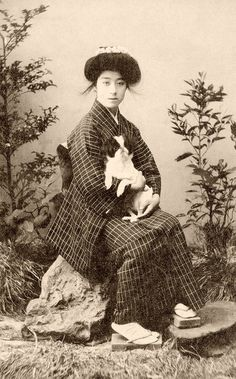 Geiko Yachiyo with a Chin Dog 1907    The Japanese Chin originated in China and was brought over to Japan around 732 CE. A favourite among 18th Century Courtesans they were called 'sleeve-dogs' or Chien de la Cour in French, as they were carried in the large sleeves of Japanese ladies.