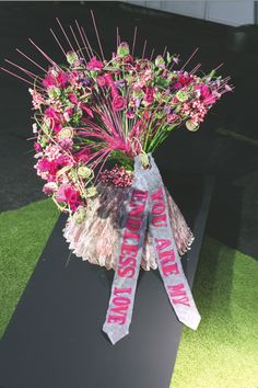 Kim Athmer van bloemsierkunst Erik in Oldenzaal maakte eerst een metalen frame. Hieraan knoopte ze lange roze pitriet-stokjes Een constructie van bind wire is over het frame gelegd en vastgezet. Hierdoor ontstaat er een speelse constructie.
