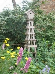 Wooden Obelisk With a Birdhouse on Top....