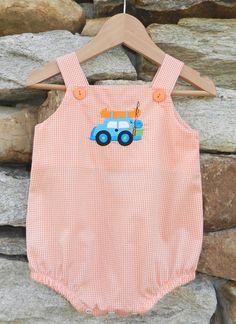 This precious one piece bubble is gathered at the leg with elastic and has snaps in the crotch for easy diaper changes. Orange gingham checks are accented with our detailed fishing jeep embroidery. Light and cool, this is an easy outfit for the summer. Straps allow room for growth. Sizes: 6m, 9m, 12m, 18m & 24m. Was: $38 Now: $24.