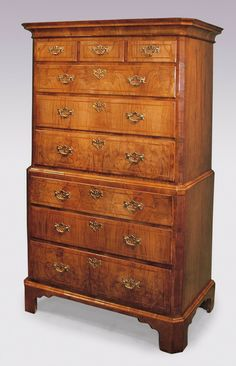 A fine George II period Walnut Tallboy having end-grain canted corner moulded cornice and crossbanded sides, having reeded canted corners to the top and bottom. The Tallboy fitted with moulded edge, herringbone banded graduated drawers retaining original handles supported on canted corner bracket feet. Circa: 1730