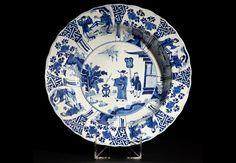 Plato con escena palaciega Plato con escena palaciega: Dignatario y sirviente China. Marca y Periodo Kangxi (1662 – 1722) Porcelana blanca y azul 34,5 cm