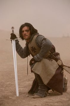 Orlando Bloom in Kingdom of Heaven. Male actor, costume, sword, kneeling, celeb, famous, portrait, photo