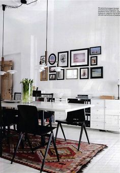 12 Kitchens & Dining Rooms Made Cozy With Kilims: This typical Copenhagen home with white floors and walls, finds strong contrast with black chairs and picture frames, along with a diamond-patterned kilim with black fringe.