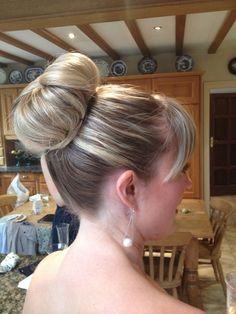 High bun created using a bun ring . HAIR by Martine