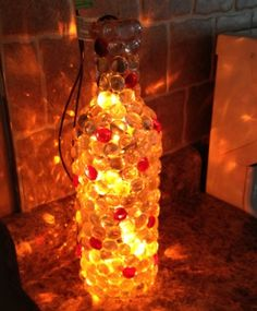 Wine Bottle Night Light:: Easy to make with a wine bottle, Christmas lights, and glass beads or pebbles. Need to add the glass pebbles. Wine Bottle Art, Lighted Wine Bottles, Bottle Lights, Wine Bottle Crafts, Glass Jars, Glass Bottle, Bead Bottle, Bottle Lamps, Crafts To Do