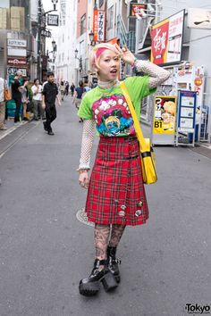 """Yappi's colorful look features a monster t-shirt over a long-sleeve net top with a tartan wrap skirt (British punk-inspired), Choco Moo x Avantgarde Harajuku graphic tights, and chunky platform boots. Accessories include a pearl choker, a pastel pony necklace, colorful bracelets, spiked bracelets, lots of rings, South Park & Spongebob buttons, and a """"Have a Happy Day"""" purse."""