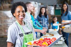 Friendly volunteer serving fresh fruit at community soup kitchen Royalty Free Stock Photo