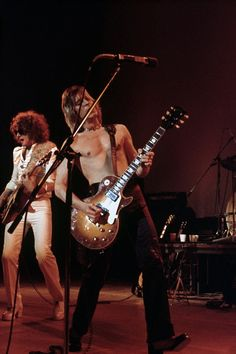 Guitarists and singers Ian Hunter and Mick Ronson perform onstage at the Ford Auditorium on April 28 1975 in Detroit Michigan