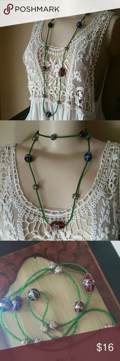 """Extra Long Glass Bead Necklace Handmade beaded necklace with green seed beads, bkue, red, black, and purple painted glass beads, and light brasstone detailed beads. Closes off with a large barrel closure. Made with Tiger string so it's durable no matter how you wear it. 20"""" length allows you to double it up or wear as a wrap bracelet. Very pretty however you like it! Handmade  Jewelry Necklaces"""