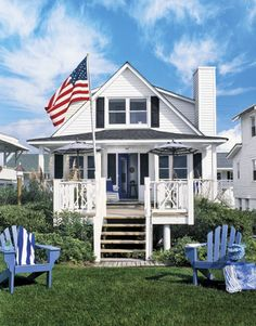 Classic Beach House  Vivid blue and bright white set the tone for a classic nautical theme, starting outside with the pair of Adirondack chairs, durable canvas market umbrellas in bold stripes, and a bright, blueberry-hued door leading inside.