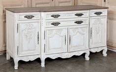 This handsome Country French buffet was crafted in Normandy, France from solid white oak to last for generations and is just the right size to store all your china, crystal and flatware, even table linens. Original solid steel hinges, drawer pulls and key guards add an authentic touch to enhance the floral and foliate bas-relief carvings. The step-front center section adds visual appeal from all angles, and is intensified by the patina painted finish below with natural weathered top. Circa…