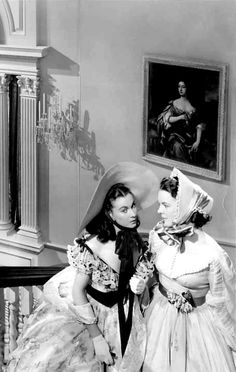 Vivien Leigh as Scarlett O'Hara and Marcella Martin as Cathleen Calvert in 'Gone With The Wind'. Scarlett has just seen Rhett Butler looking at her at the Twelve Oaks barbecue and asks her friend who he is.