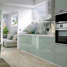 Une grande cuisine équipée de portes et tiroirs brillants. Assemblée avec des électroménagers aux finitions d'acier.